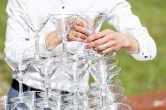 Kellner errichtet eine Pyramide von Gläsern für Champagner Stockfoto