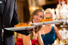 Kellner gedientes Abendessen in einem feinen Restaurant Stockbilder