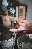 Kellner gießt ein Getränk in einen Jigger Stockbilder