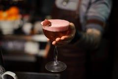 Kellner hält saure Mischungskirsche des alkoholischen Cocktails Stockfotos