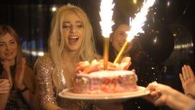 Kellner holen zu einem glücklichen Mädchen Kuchen mit Feuerwerk an der Geburtstagsfeier in einer Dunkelkammer mit Freunden 25 Jah stock video footage