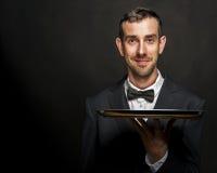 Kellner im schwarzen Anzug, der Behälter über schwarzem Hintergrund hält stockfotos