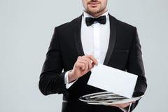 Kellner im Smoking mit dem bowtie, das leere Karte auf Behälter hält stockfotografie