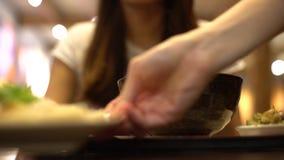 Kellner 4K dient traditionelle chinesische Nahrung während die asiatische Frau, die Smartphone verwendet stock video