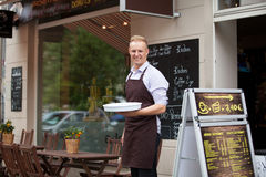 Kellner mit einem Behälter in einer Kaffeestube Lizenzfreie Stockfotos