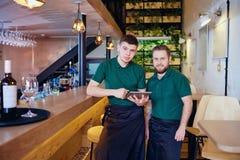 Kellner mit zwei Barmixern mit einer Gerättablette in der Stange Stockfotografie