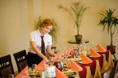 Kellner nahe der Tabelle mit Lebensmittel Lizenzfreie Stockfotos