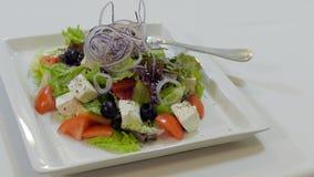 Kellner Puts eine Platte mit griechischem Salat auf einer Tabelle stock video