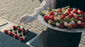 Kellner setzt Canape mit Kirschtomaten und -käse auf eine Platte auf Verpflegung stock video