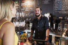 Kellner Taking Female Customers Bestellung in der Kaffeestube stockfoto