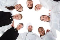 Kellner und Kellnerinnen, die im Kreis stehen Stockbild