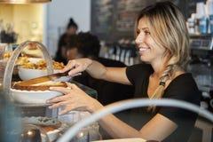 Kellnerin-Behind Counter In-Kaffeestube-Ausschnitt-Scheibe des Kuchens stockfoto