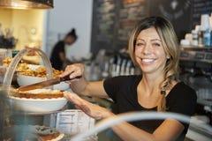 Kellnerin-Behind Counter In-Kaffeestube-Ausschnitt-Scheibe des Kuchens lizenzfreie stockfotografie