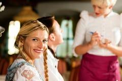 Kellnerin in der bayerischen Gaststätte, die Ordnungen nimmt Stockbilder