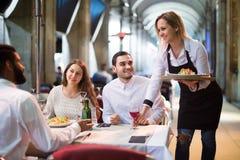Kellnerin, die Bestellung am Terrassentisch am Sommertag holt Stockfotos