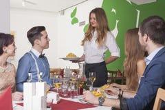 Kellnerin, die den Gästen im Restaurant eine Mahlzeit dient Lizenzfreie Stockfotografie