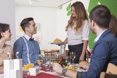 Kellnerin, die den Gästen im Restaurant eine Mahlzeit dient Stockbilder
