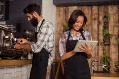 Kellnerin, die digitale Tablette während Kellner zubereitet Kaffee im Hintergrund verwendet stockfotos