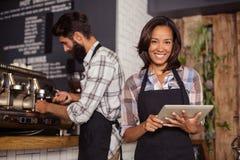 Kellnerin, die digitale Tablette während Kellner zubereitet Kaffee im Hintergrund verwendet lizenzfreie stockfotografie