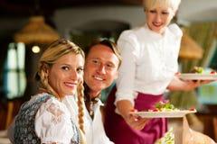 Kellnerin, die eine bayerische Gaststätte dient Lizenzfreies Stockbild