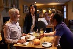 Kellnerin, die einen Nachtisch zu einem männlichen Paar in einem Restaurant dient lizenzfreie stockfotos
