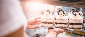 Kellnerin, die Kuchen vereinbart Stockfotografie