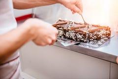 Kellnerin, die Kuchen am Verkaufsmöbel vereinbart Lizenzfreie Stockfotos