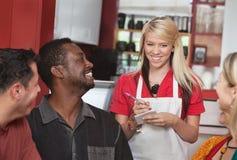 Kellnerin, die Ordnungen am Café nimmt Stockfotos