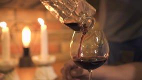 Kellnerin, die Rotwein in Glas während romantisches Abendessen mit Kerzen im Restaurant gießt Strömender Wein der Kellnerin von d stock footage
