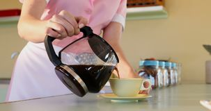 Kellnerin, die schwarzen Kaffee in der Schale am Restaurant 4k gießt stock video