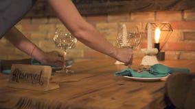 Kellnerin, die Weinglas auf Tabelle für romantisches Abendessen mit Kerzen in Luxusrestaurant einsetzt Dienende Tabelle in romant stock footage