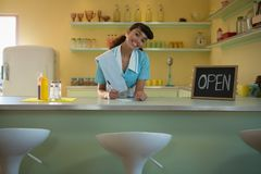 Kellnerin, die am Zähler im Restaurant steht Stockbild