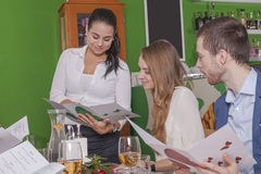 Kellnerin empfiehlt Mahlzeiten ihren Gästen stockbild