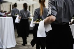 Kellnerin trägt Platten des Lebensmittels Stockbilder