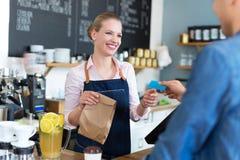Kellnerinumhüllungskunde an der Kaffeestube Stockfotos
