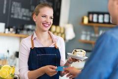 Kellnerinumhüllungskunde an der Kaffeestube Lizenzfreies Stockfoto