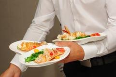Kelnerów chwytów talerze z homarami Zdjęcia Stock