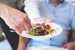 Kelner die een plaat van Griekse salade dienen Royalty-vrije Stock Foto