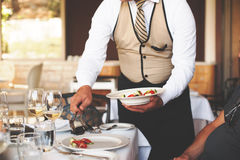 Kelner die een plaat van salade dienen aan een mensengast in een restaurant Royalty-vrije Stock Afbeeldingen