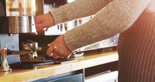 Kelner die koffiemolen met behulp van om koffiebonen te malen stock footage