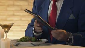 Kelner die menu of rekening geven aan rijke man, bedrijfslunch, de restaurantdienst stock footage
