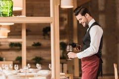 Kelner die rode wijn gieten royalty-vrije stock afbeelding
