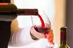 Kelner die rode wijn gieten Stock Foto's