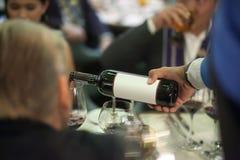 Kelner die rode wijn in wijnglas gieten op de lijst voor de dienst royalty-vrije stock afbeelding