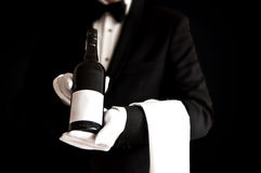 Kelner die in smoking een fles rode wijn houdt Stock Fotografie