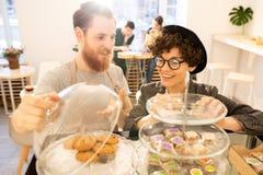 Kelner die snoepjes voorstellen aan klant in koffie royalty-vrije stock afbeelding