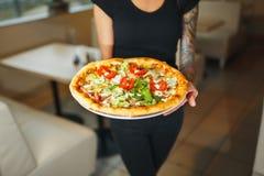 Kelner die twee verschillende platen met een smakelijke pizza dragen Foto met pizza twee Pizza met paddestoelen en pizza met sala stock foto