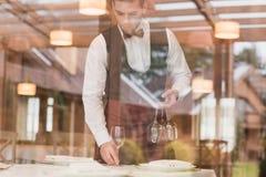 Kelner die wijnglazen op lijst zetten Stock Fotografie