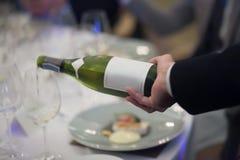 Kelner die witte wijn gieten in het wijnglas in restaurant royalty-vrije stock afbeeldingen