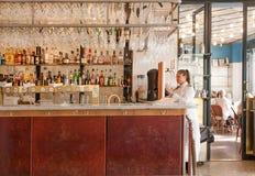 Kelner die zich dichtbij bar couner met alcoholflessen bevinden binnen modern stijlrestaurant Stock Afbeeldingen